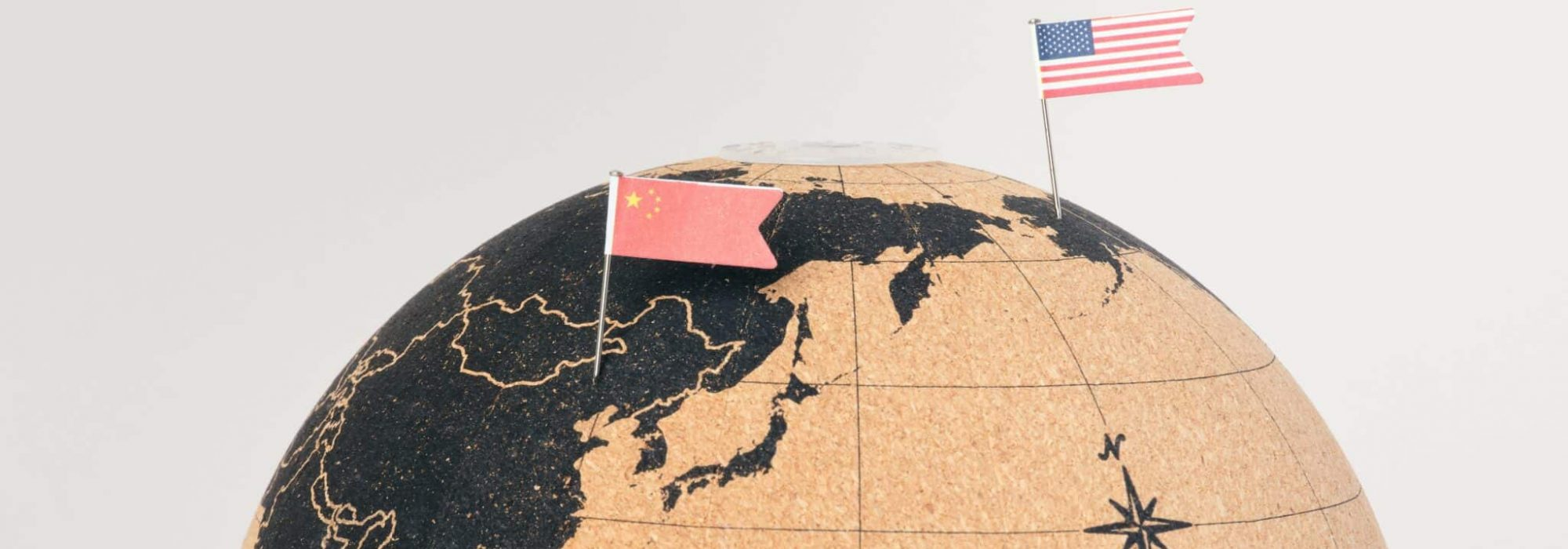 The US and China flags on a globe.