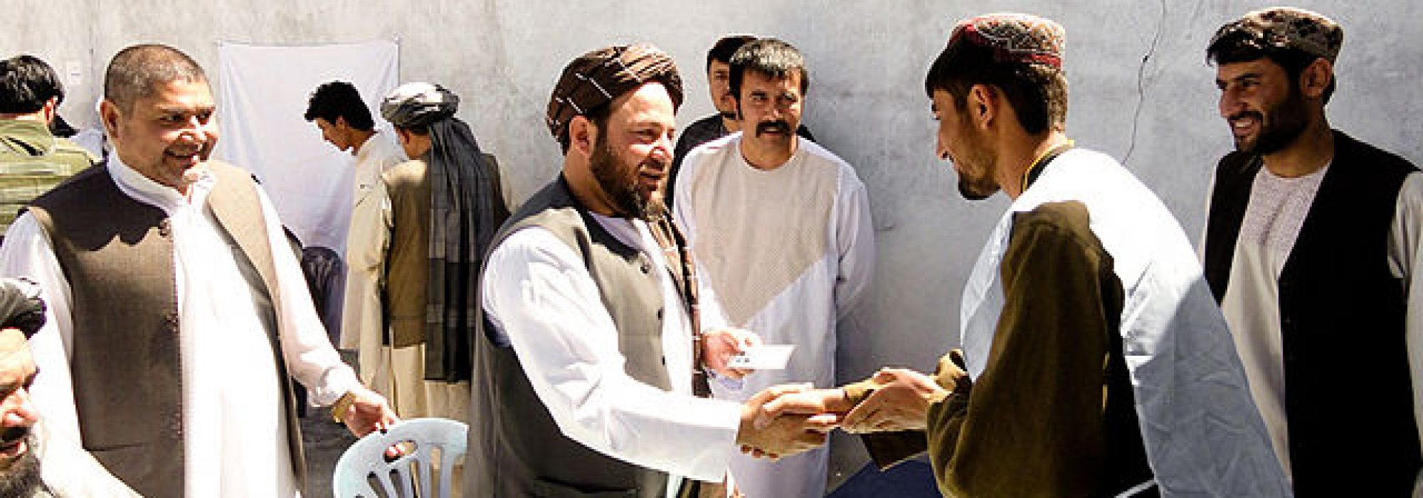 Amir_Mohammad_Akhundzada,_center,_the_governor_of_Uruzgan_province,_Afghanistan,_presents_a_new_voter_registration_card_to_a_Tarin_Kowt_resident_in_the_province_May_26,_2013_130526-D-ZZ999-001