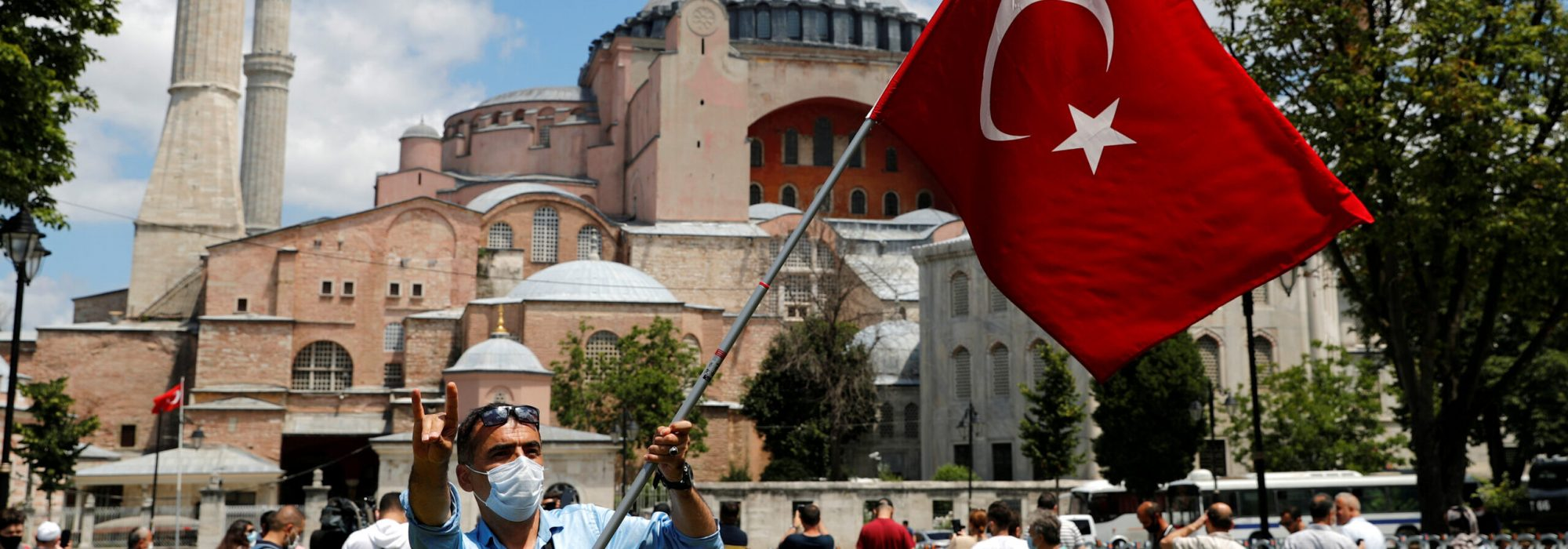 A man waves a Turkish flag as he makes the nationalist grey wolf sign in front of the Hagia Sophia or Ayasofya-i Kebir Camii in Istanbul, Turkey, July 17, 2020.,Image: 544183014, License: Rights-managed, Restrictions: , Model Release: no, Credit line: MURAD SEZER / Reuters / Forum